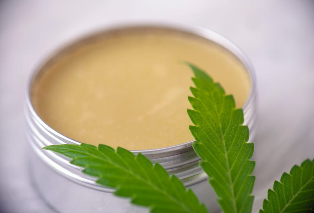 cannabis salve jar next to leaf, salves and topicals are a good cannabis delivery method