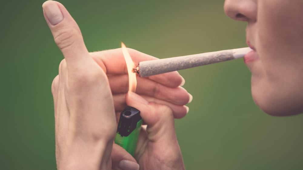 woman lighting a large joint to smoke, a popular cannabis delivery method