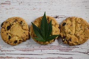three chocolate chip cookie edibles with a marijuana leaf placed on top of the cookie in the center