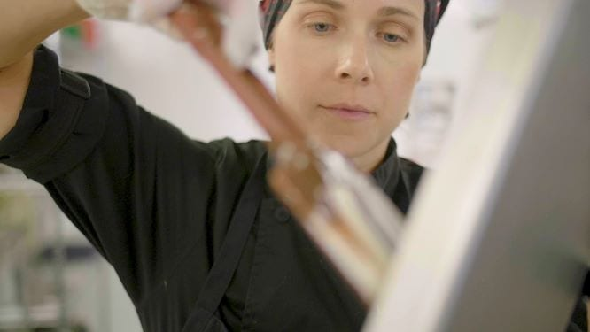 image of chocolatier at coda using a spatula to work the chocolate edibles