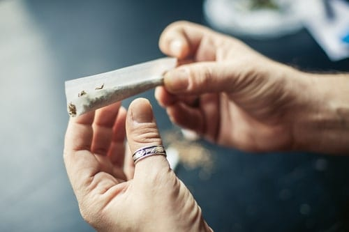 a man rolling a weed joint