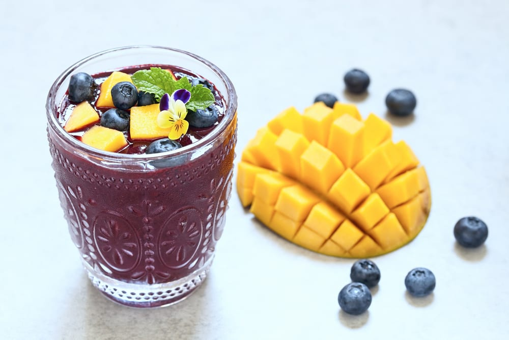 blueberry mango smoothie in glass with mango and blueberry garnish