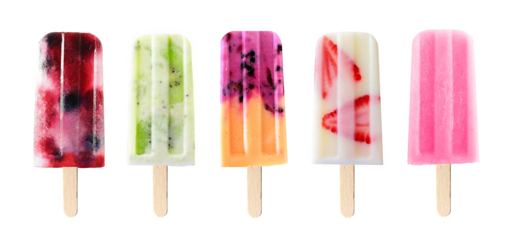 fruit popsicles lined up on a white background