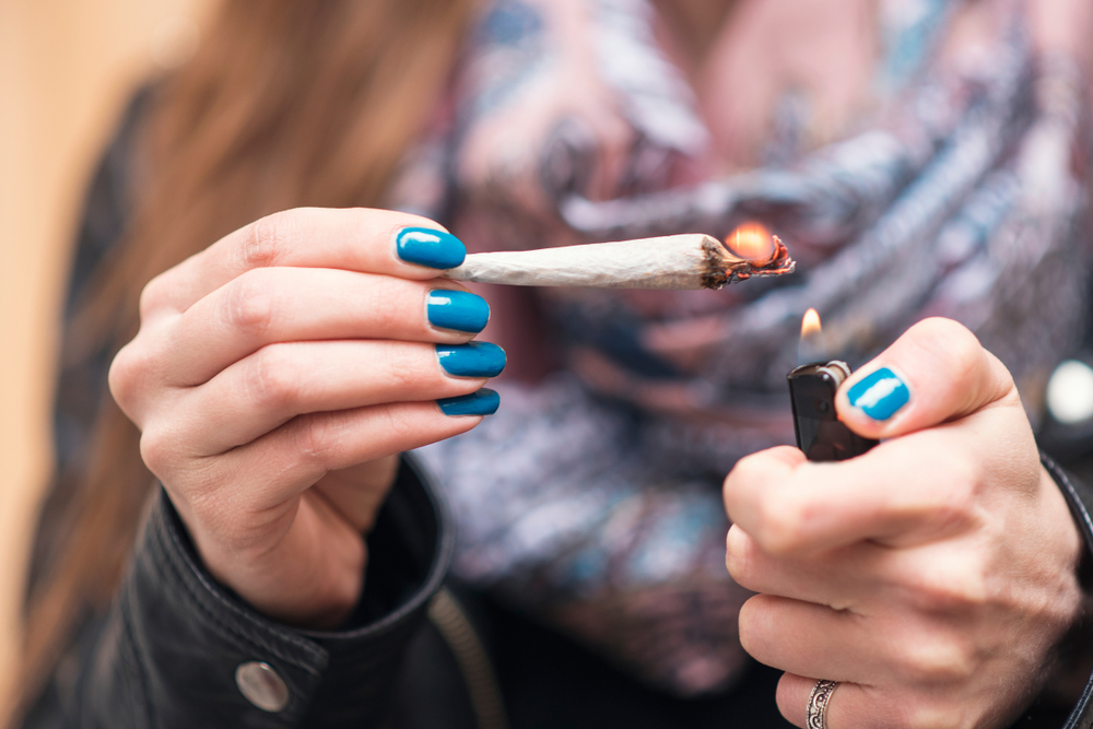 woman lighting marijuana joint end