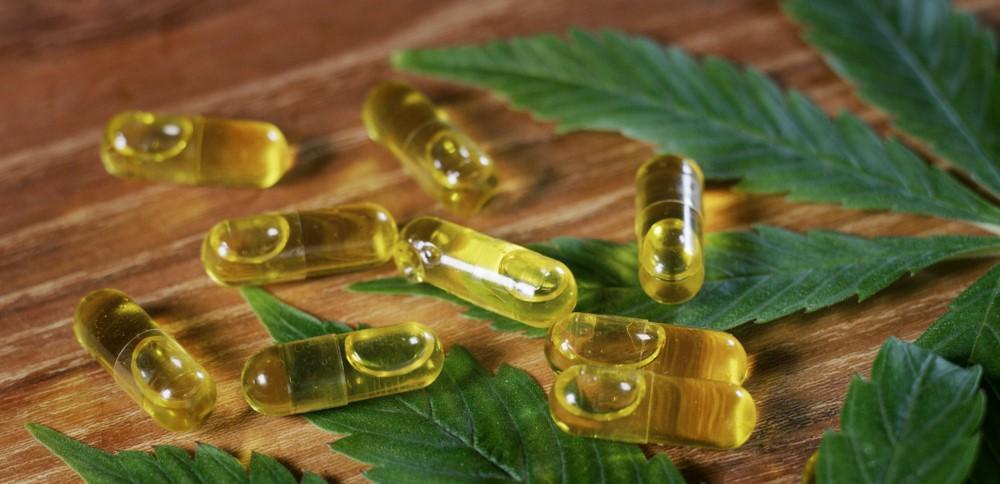 cannabis capsules on marijuana leaves