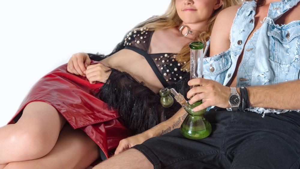 high couple smoking bong laying down together