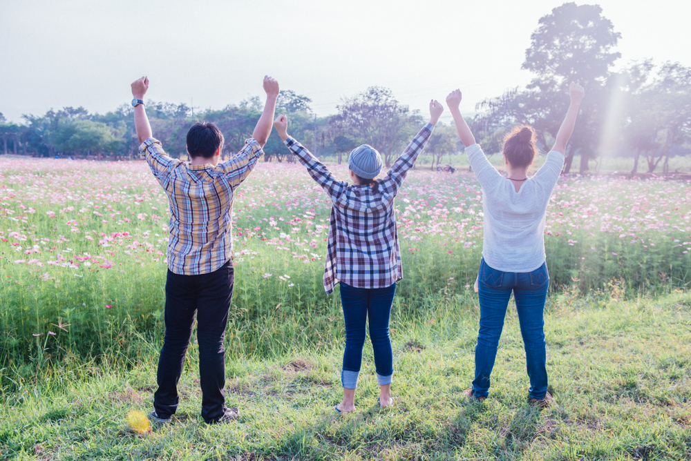Volunteers look at a field of flowers with arms in the air